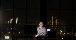 De mens van de bureaumanager werkt overwerk het typen aan toetsenbord laat bij nacht stock video