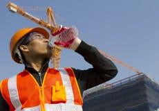 De mens van de arbeider aangezien hij van een plastic waterfles drinkt Royalty-vrije Stock Foto's