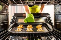 De mens van de bakselpeperkoek in de oven stock afbeeldingen