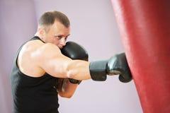 De mens van de bokser bij het in dozen doen opleiding met zware zak Stock Afbeelding