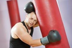 De mens van de bokser na het in dozen doen opleiding met zware zak Stock Foto's