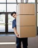 De mens van de levering in eenvormige dragende stapel dozen Stock Fotografie