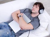 De mens van de slaap met hoofdtelefoon en laptop royalty-vrije stock foto's