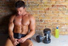 De mens van de spier die met gewichten en drank wordt ontspannen stock fotografie