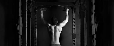 De mens van de spieratleet in gymnastiek die verhogingen maken Stock Foto's