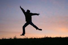 De mens van de sprong op zonsondergang Royalty-vrije Stock Fotografie
