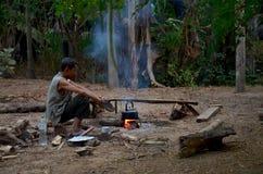 De mens van de Thaise etnische zitting van Phu op de boomstam en kookt water met royalty-vrije stock fotografie