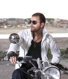 De mens van Hansom op een motorfiets Stock Foto's
