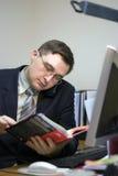 De mens van het bureau leest een boek Royalty-vrije Stock Afbeeldingen