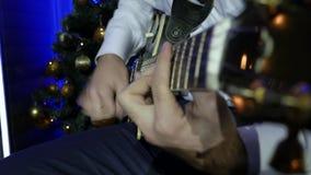 De Mens van het Kerstmisoverleg het spelen gitaar stock videobeelden