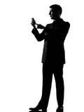 De mens van het silhouet op het overseinen van de telefoon sms tekst Royalty-vrije Stock Afbeeldingen