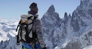De mens van de klimmerbergbeklimmer sneeuw bereiken zet bovenkant met ijsbijl in op zonnige dag De activiteit van de alpinismeski stock video