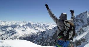 De mens van de klimmerbergbeklimmer sneeuw bereiken zet bovenkant met ijsbijl in op zonnige dag De activiteit van de alpinismeski stock videobeelden