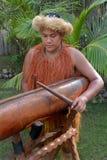 De mens van kokIslander speelt muziek binnen op een grote houten trommel van de logboekpastei stock fotografie