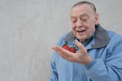 De mens van oudsten met aardbeien Stock Afbeeldingen