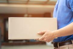 De mens van de pakketlevering van een pakket door de dienst verzendt naar huis stock foto's
