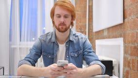 De Mens van de roodharigebaard het Typen Bericht op Smartphone, SMS of E-mail stock videobeelden