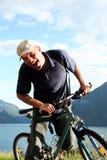 De mens van Shoutinng op de fiets stock foto