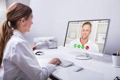 De Mens van tandartsvideo conferencing with op Computer stock foto's