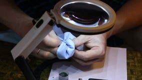 De mens veegt een juwelier gouden ring na het oppoetsen af stock video