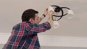 De mens verandert een gloeilamp in kroonluchter op plafond stock video