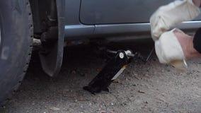 De mens verandert het wiel op de auto op de weg stock video