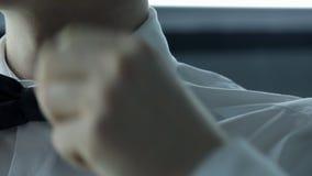 De mens verbetert zijn donkere vlinderdas op wit jasje binnen stock video