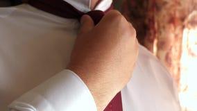 De mens verbindt rode band Close-up De zakenman zet op een band aan het werk in de ochtend De beambte wordt gekleed in stock videobeelden