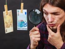 De mens verifieert geldcontant geld Royalty-vrije Stock Afbeeldingen