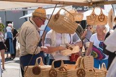 De mens verkoopt rieten manden op een markt Stock Foto