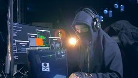 De mens in vermomming binnendringt in een beveiligd computersysteem in het netwerk van de computer stock videobeelden