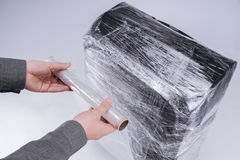 De mens verpakt koffer beschermende film Stock Fotografie