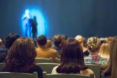 De mens verschijnt op stadium in theater met vele mensen royalty-vrije stock foto's