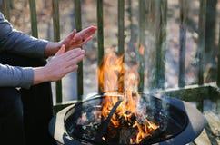 De mens verwarmt Zijn Handen over een Brandkuil op een Dek stock fotografie