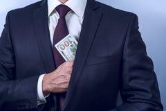 De mens verwijdert Amerikaanse dollars in zijn kostuumzak stock foto