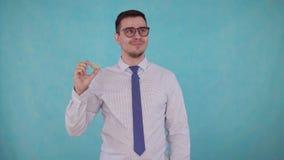 De mens verwijdert het gehoorapparaat van zijn oor en hoort op blauwe achtergrond stock footage