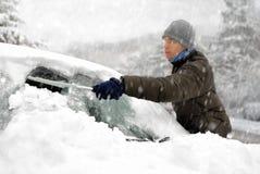 De mens verwijdert sneeuw uit zijn auto Stock Afbeelding