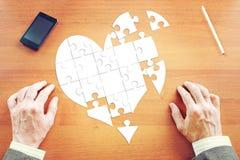 De mens verzamelt een hart zoals raadsels op het bureau Royalty-vrije Stock Fotografie