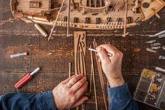 De mens verzamelt het voertuigmodel op de houten lijst Stock Foto