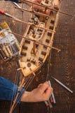 De mens verzamelt het voertuigmodel op de houten lijst Stock Fotografie