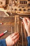 De mens verzamelt het voertuigmodel op de houten lijst Stock Afbeeldingen