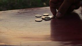 De mens verzamelt muntstukken op lijst stock videobeelden