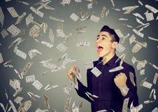 De mens viert succes onder geldregen die onderaan dollarbankbiljetten vallen Royalty-vrije Stock Afbeelding