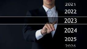 De mens vindt het jaar van 2023 in virtueel archief, inzameling van statistieken, jaarverslagen royalty-vrije stock afbeelding