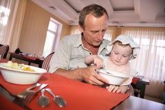 De mens voedt het kind stock afbeelding