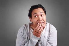 De mens voelt Doen schrikken terwijl het Bijten van zijn Vinger Stock Foto