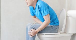 De mens voelt pijn met constipatie stock fotografie