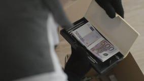 De mens vond het geld in de doos De mens zoekt iets in een doos stock foto