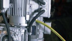 De mens vouwt de kabel in de automatische kabelsnijmachine Automatische robotachtige complexe besnoeiingen de kabel stock video