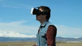 De mens in 360Vr-Helm bij de Meerbank gaat weg Jonge Mens in Park in Autumn Landscape Watching Video 360 Graden binnen stock footage